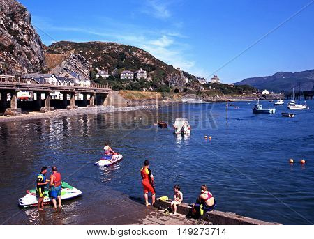 BARMOUTH, UNITED KINGDOM - AUGUST 6, 1995 - Holidaymakers enjoying water sports with views towards the railway bridge and mountains Barmouth Gwyedd Wales UK Western Europe, August 6, 1995.