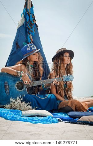 Two Beautiful Gypsy Girls With Guitar Sitting On Pillows At Tepee On Sea Shore