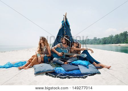 Attractive Boho Man And Women Sitting On Pillows At Tepee On Beach. Youth And Happiness.
