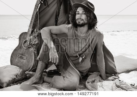 Attractive Young Boho Man With Guitar Sitting On Pillows At Tepee