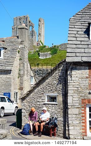 CORFE, UNITED KINGDOM - JULY 19, 2016 - Couple sitting on a bench in village centre with the castle to the rear Corfe Dorset England UK Western Europe, July 19, 2016.