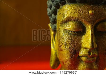 Gold Buddha face on dark red background