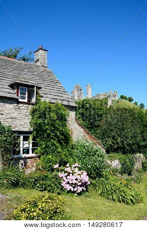 Pretty stone cottage with the castle to the rear Corfe Dorset England UK Western Europe.