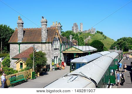 CORFE, UNITED KINGDOM - JULY 19, 2016 - Passengers boarding LSWR T9 Class 4-4-0 steam train and BR Class 108 diesel train in the railway station with the castle to the rear Corfe Dorset England UK Western Europe, July 19, 2016.