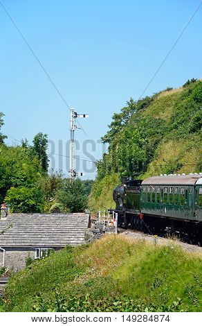 CORFE, UNITED KINGDOM - JULY 19, 2016 - LSWR T9 Class 4-4-0 steam train at the railway station with the engine driver looking out of the cabin Corfe Dorset England UK Western Europe, July 19, 2016.