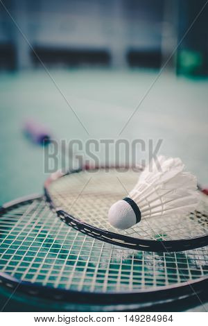 Badminton ball (shuttlecock) and racket on court floor vintage tone. Badminton ball (shuttlecock) and racket on court floor. Badminton sports. Play badminton. Badminton exer cise. Badminton tournament. Badminton training. Badminton feather. Badminton heal