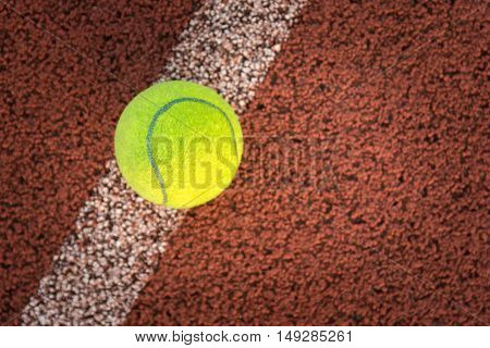 Close up of tennis ball on clay court./Tennis ball, Tennis court, Tennis ball, Tennis racket, shadow tennis, Tennis sport, Tennis concept, Tennis ball green color,