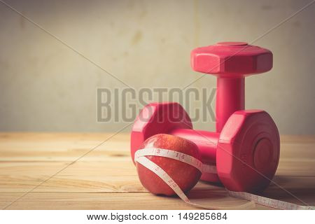 apple and measuring tape and Pair of red 1 kg dumbbells on wooden vintage tone