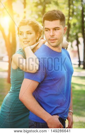 Portrait of couple in love walking in sun autumn park. In love girl embrace gay. Man and woman in love outdoor. Love in park.
