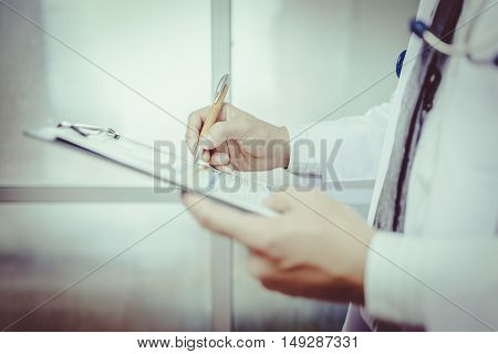 Close-up Of Male Doctor Filling The Medical Form vintage tone. Doctor man. Doctor woman. Doctor writting. Doctor room. Uniform doctor. Doctor working.