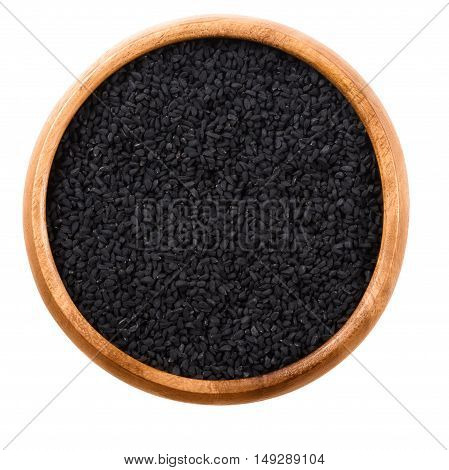Black cumin seeds in wooden bowl over white. Dried whole fruits of Nigella sativa, also black caraway, nigella or kalonji. Used as a spice in Indian and Middle East cuisine. Isolated macro food photo.