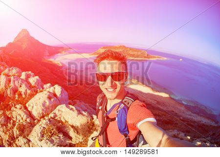 man traveler with backpack standing on the cliff against sea and blue sky at early morning. Balos beach on background, Crete, Greece. man taking a selfie