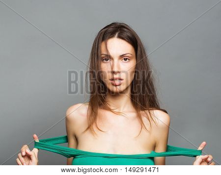 young sexy fashionable woman or girl with long brunette hair and pretty face in stylish green dress with bare shoulders in studio on grey background