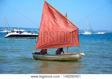 STUDLAND BAY, UNITED KINGDOM - JULY 19, 2016 - People sailing in a dinghy near the beach Studland Bay Dorset England UK Western Europe, July 19, 2016.