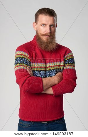 Serious confident bearded hipster man in woolen sweater standing with folded hands and looking at camera, studio portrait over grey background