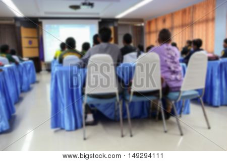 student learning business sitting in room with teacher front and white projector slide screen Blur blurred view from back of the classroom