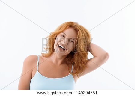 Shy middle-aged woman is laughing with joy. She is standing and touching her red hair. Isolated