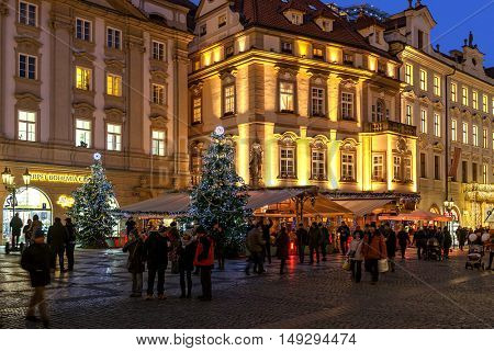 PRAGUE, CZECH REPUBLIC - DECEMBER 10, 2015: People walking by illuminated buildings and restaurants decorated for Christmas holidays in Old Town of Prague during traditional winter market.