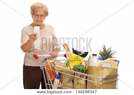 Mature woman looking at a store receipt isolated on white background