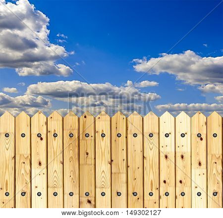 Detail of a wooden fence built with spiky wooden boards against a blue sky