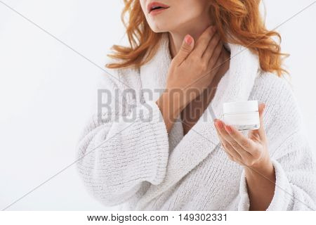 Elegant middle-aged woman is applying cream on her neck with pleasure. She is standing and holding jar. Isolated