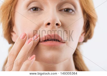 Calm middle-aged woman is standing and touching her skin near lips. She is looking forward with relaxation. Isolated