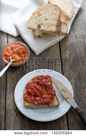 Slice of bread smeared with homemade chutney on wooden table