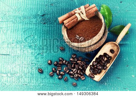 Roasted coffee beans with ground coffee and cinnamon sticks on blue wooden background. Copy space