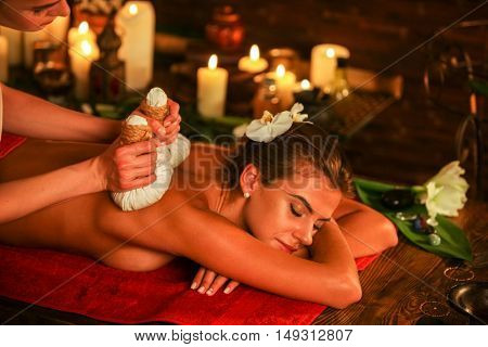 Young woman lying on wooden spa bed. Poultice hot herbal massage in spa salon. Burning candles on bachground.