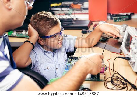 Little boy and teacher in class with electronic project