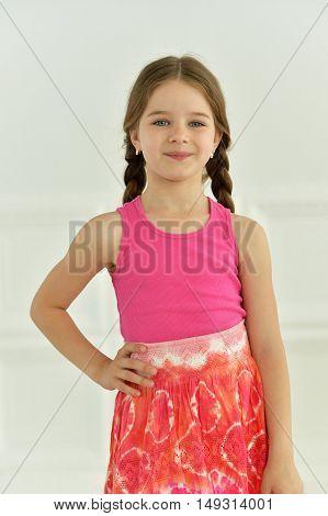 portrait of cute little girl posing in bright dress