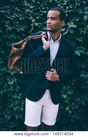 Confident in his perfect style. Handsome young African man in smart casual wear carrying bag on shoulder and looking away while standing against green plant background outdoors