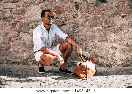 Perfect style. Handsome young African man in smart casual clothes crouching near his bag and with stoned wall in the background