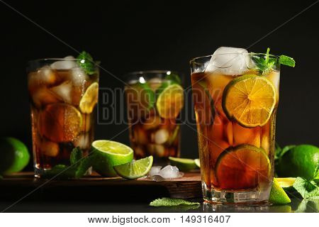 Cuba libre cocktail with lime, ice and mint on dark background