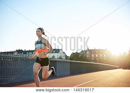 Fit muscular young woman runner sprinting across an urban bridge with receding perspective and a bright sunrise with copy space