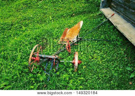 Old Rusty Farmers Tiller in Empty Field, Green Grass