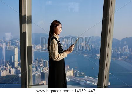 Female CEO is watching news in internet via touch pad while is standing in office interior near window with view of business district. Young Chinese woman manager is using for work digital tablet