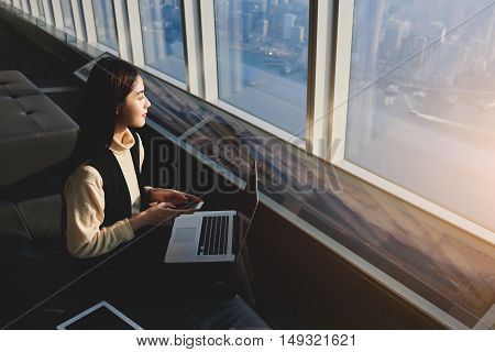 Japanese businesswoman is thinking about future meeting with international partners while is sitting with mobile phone and net-book in loft with contemporary design with China city outside the window