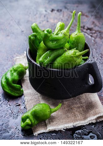 Food and drink, still life, moody concept. Raw green peppers pimientos de padron mexican jalapeno traditional spanish tapas on a black rusty table. Selective focus