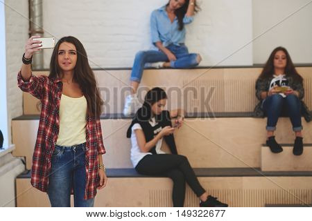 Young woman student is making photo on mobile phone with front camera of a her fiends while they are sitting in university. Attractive hipster girl with cool look is shooing video on cell telephone