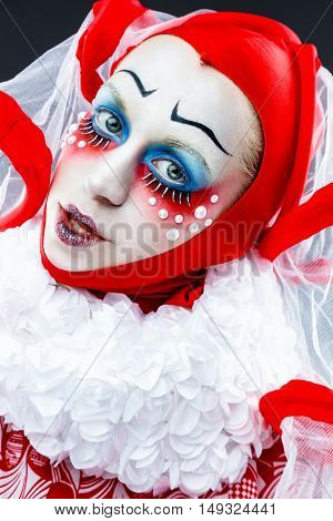Close up portrait of female clown in a vintage style with a typical makeup on white background