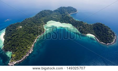 Aerial photo from flying drone of green island with tropical plants in open sea in summer sunny day in Thailand. Beautiful landscape of nature with Indian Ocean. Perfect background for travel website