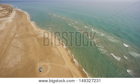 Aerial photo from flying drone of a beauty nature scenery with calm sea and sandy beach with blue boat in sunny summer day in Thailand. Amazing landscape with Indian Ocean during trip to Bali