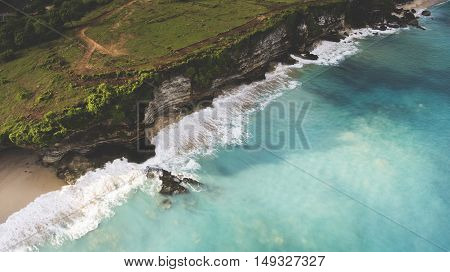 Aerial photo from flying drone of a green island with rocky cliff near Indian Ocean with swell waves an ideal place for surfing training. Beautiful nature landscape with dreamland beach and calm sea