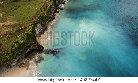 Aerial photo from airplane of a wonderful landscape island with clean sandy shore. Rock cliff on dreamland Bali beach with beautiful blue color of sea water. Background with copy space for website