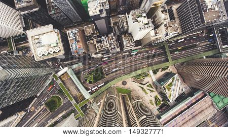 Top view aerial photo from flying drone of a developed Hong Kong city with modern skyscrapers with contemporary design. China town with business and financial centers and road with cars