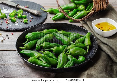 Food and drink, still life, moody concept. Raw green peppers pimientos de padron mexican jalapeno traditional spanish tapas on a wooden table. Selective focus poster