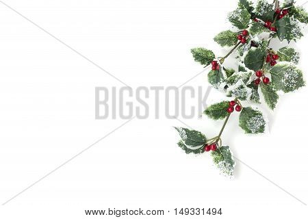 Artificial holly branch - ilex aquifolium with fruits glass stones and glitter isolated on white background with copy space.