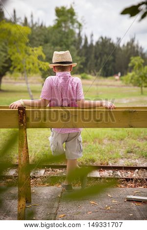 Cute kid boy in straw hat standing on rails back to a camera in field in the summer. Child on old railroad.