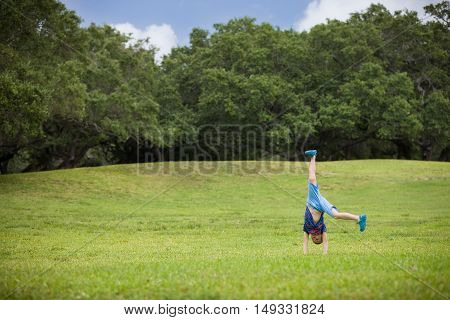 Cute kid boy standing on hands outside on a sunny summer day. Child doing somersault on grass meadow in the park. Active children outdoors.